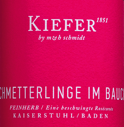 """The Schmetterlinge im Bauch Rosé from Weingut Kiefer from the series """"Young Poets"""" shines with a wonderful raspberry-pink in the glass. To the eye, a dreamlike rosé wine with an intense color reveals a lively and exciting scent of red fruits like raspberry, strawberry and red currant, complemented by meadow flowers and citrus nuances. On the palate, this German rosé wine is dominated by ripe raspberries and red currants. A delicate tingle, combined with a hearty sweetness-acidity play exudes pure joie de vivre and guarantees an uncomplicated and wonderfully fruity drinking pleasure. After """"real"""" butterflies in the stomach, this wine is the next best thing. The best is of course the combination of both versions. Vinification of the Schmetterlinge im Bauch Rosé Wine The Schmetterlinge im Bauch wine is vinified from Pinot Noir, Dornfelder, Cabernet Mitos, and Cabernet Carol and finished with subtle residual sweetness. The grapes grow on mineral loess soils with volcanic rock underneath. Drinking recommendation for the Schmetterlinge im Bauch wine Enjoy the Kiefer Schmetterlinge im Bauch Rosé as a perfect summer wine on the terrace in the evening or as a nice companion to Mediterranean fish dishes. It also makes an excellent Valentine's Day wine. Charming: If you're so caught up that you can't talk anymore, just put the bottle in your hand ;-)"""