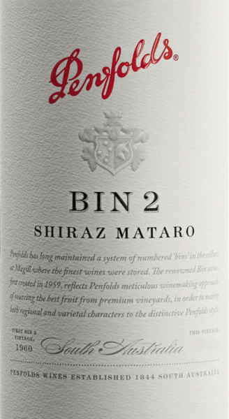 Bin 2 by Penfolds is a concentrated, full-bodied red wine cuvée from the Mataro and Shiraz grape varieties. The grapes for this red wine grow in the Australian wine-growing region South Australia. In the glass, this wine reveals a deep dark, strong black-red colour with a deep, purple core. This cuvée shows a warm spicy, aromatically robust bouquet with hints of figs, dates, plums (prunes), quince paste and cake spices. Notes of preserved blueberries and blackberries and leather underline the aromas of the nose. On the palate, this Australian red wine is full and velvety with a medium to full body and a taste reminiscent of rich berry fruit and warm chocolate aromas. Subtle oak notes and sophisticated integrated, fine-grained, almost powdery tannin are added in the background. A fresh acidity and a long, chunky finish with a spicy aftertaste of dark berries perfect this wine. Vinification of the Shiraz Mataro Bin 2 Penfold The Shiraz and Mataro grapes are separated, harvested, selected and vinified separately according to origin. The mash is fermented in stainless steel tanks in the Penfolds wine cellar and after the fermentation process has been completed, this wine matures for 8 months in French oak barriques (10% new wood) and in American oak hogsheads. After the woodwork, this wine is married to the final blend and rests for some time on the bottle in the wine cellars before this red wine leaves the Penfolds winery. Food recommendation for the Bin 2 Penfolds We recommend this dry red wine from Australia with gently braised meat and poultry with tomatoes such as Osso buco, Coniglio alla cacciatora (hunter-style rabbit), veal roulades in tomato sauce or chicken basquais (Basque chicken), Provençal beef ragout (in red wine sauce), roasted rabbit with prunes, gratinated aubergines or ratatouille.